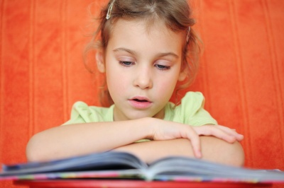 The girl reads the book focuses