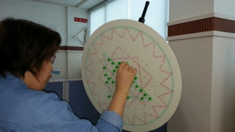 Five months later, Su-Jin's improved visual awareness allowed her to locate more spaces to place green pegs in the center of the board.